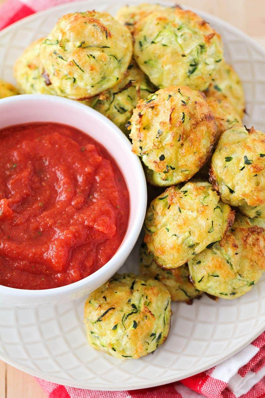 Cheesy Zucchini Tots on a white plate with marinara